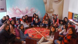 Group of mother-daughter pairs (girls 10-12 years) seated around a red velvet circle in a workshop room with a mural behind them