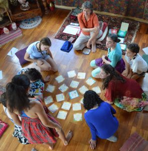 GGroup of 10-12 year old girls gathered around activity cards on the floor